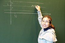 young female researcher in front of blackboard